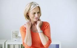 Frau mit Schmerzen im Nacken-Schulterbereich